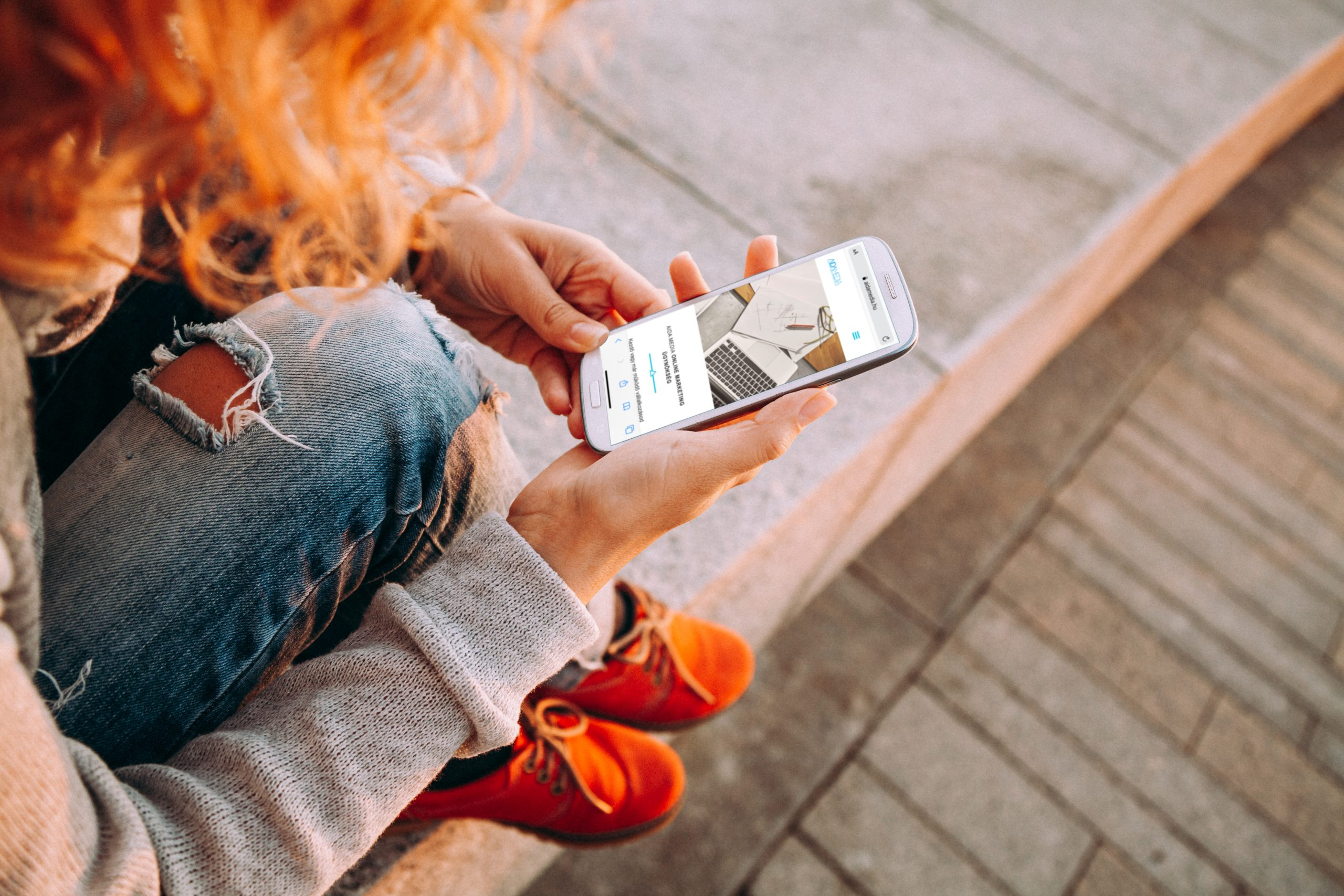 social media marketing felületet néz mobilon egy nő